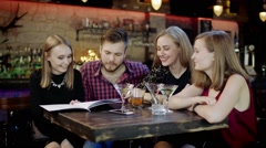 Happy young people sitting in the bar reading menu card - stock footage