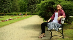 Young Woman Sitting Outside Yawning And Streching Arms - stock footage