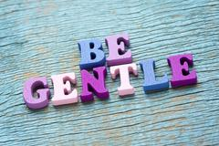 Be gentle phrase on vintage wooden background Stock Photos