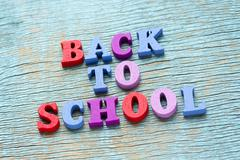 Back to school phrase on vintage wooden background Stock Photos