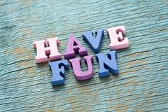 Have fun phrase on vintage wooden background Stock Photos