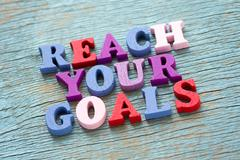 Reach your goals phrase on vintage wooden background - stock photo