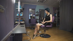 Punk girl with blue hair and tattooed legs in a beauty salon Stock Footage