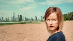 Girl on the beach looking at urbanization - as the city survive nature Stock Footage