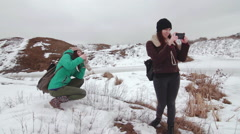 Girls take pictures of each other in snowy field Stock Footage