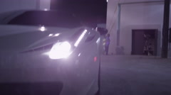 Sweep across the front of a high-end Porsche as it reverses. Arkistovideo