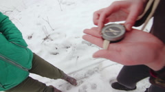 Two girls define the compass where to go in the snowy field Stock Footage