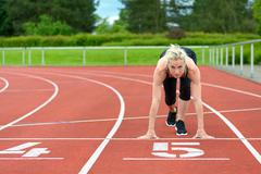 Athletic woman in the starter position on a track - stock photo