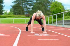 Single woman stretching calf muscles at race track - stock photo