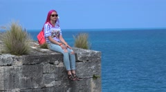Girl with pink hairs sits on the edge of the fort wall and looks at the sea. Stock Footage