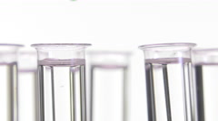 pipette depositing drops of blue dye in rotating test tubes - stock footage