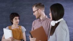 4K Portrait smiling group holding books & computers on chalkboard background Stock Footage