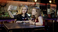 two young women is taking selfie and clinking glasses in the bar - stock footage