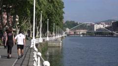 People walking along the river in Bilbao, Spain Stock Footage