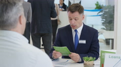 4K Modern city bank, man assisting customer & getting signature on document - stock footage