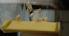 Shallow focus close up of popcorn kernels popping in a yellow machine. Isolated. Stock Footage