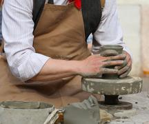 craftsman potter shaping clay to make a beautiful vase handmade - stock photo