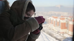 Beautiful woman takes photos of the winter city from a height Stock Footage
