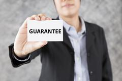 Businessman presenting business card with word guarantee Stock Photos