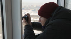 A beardless man with compact camera takes pictures of the winter city from the Stock Footage