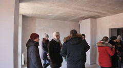Group of warmly dressed designers and architects in an unfinished room Stock Footage