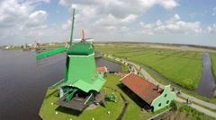 Aerial bird eye view Zaanse Schans turning around green windmill 4k Stock Footage