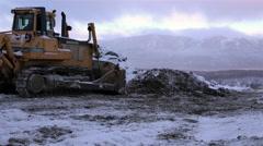Village Milkovo, Bulldozer working on the top of huge pile Stock Footage