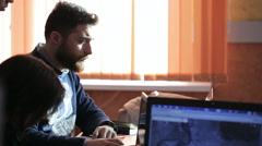 Bearded man looks at the laptop screen and asks other people about something Stock Footage