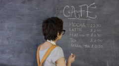 4K Portrait of smiling cafe worker writing drinks menu on chalkboard Stock Footage