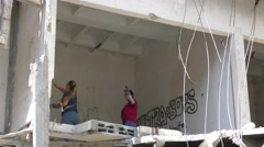Volunteers seek injured fruit bats in the rubble after habitat was demolished - stock footage