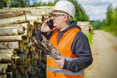 Lumberjack with tree bark and smart phone near log of pile - stock photo