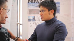 A man wearing glasses and a gray blue sweater actively gesticulating, telling - stock footage
