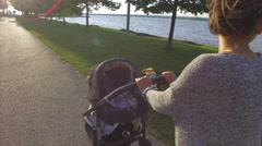 Attractive mother pushes stroller on path in front of water - stock footage
