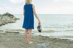 Barefoot girl standing on the beach and looks into the distance Stock Photos
