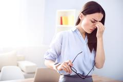 Cheerless tired woman standing in the office - stock photo