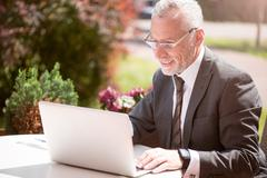 Positive businessman sitting at the table - stock photo