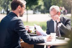 Concentrated colleagues sitting at the table - stock photo
