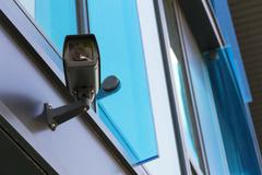 Grey security camera attached to wall blue windows in background - stock photo