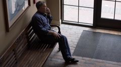 Mature man sitting on a bench in an old hotel using his cell phone 4k Stock Footage