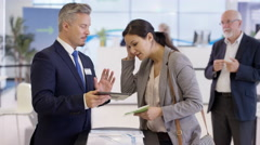 4K Friendly bank workers talking to customers & offering financial advice Stock Footage