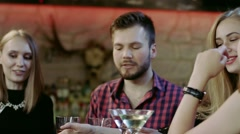 company of young friends is clinking glasses in the bar - stock footage