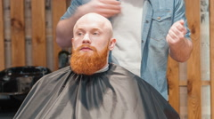 Professional barber styling beard of his client Stock Footage