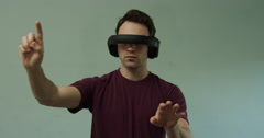 Young man in virtual reality headset scrolls and turns imaginary dials Stock Footage