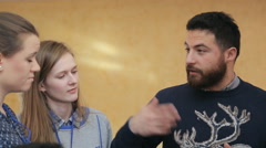 A bearded man in a sweater, gesturing, urges two girls in expediency of his Stock Footage