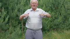 Old man does morning exercises stretches hands fingers in park with conifers - stock footage