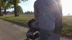Father pushes baby stroller along beach while watching volley ball Stock Footage