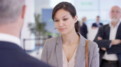 4K Friendly bank worker talking to customer & offering advice about a loan - stock footage