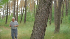 Old man running in the park then resting near tree stem and looking on a camera - stock footage