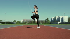 Young woman exercises using a jump rope Stock Footage