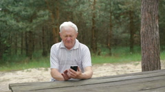 The old man uses the phone at the table in the forest - stock footage